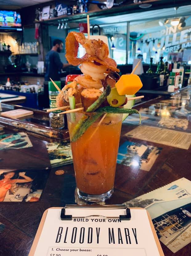 A glass with bloody mary and additions of cheese, olives, bacon, shrimp, sausage on tooth picks on the bar with a Bloody Mary menu.