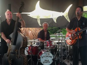 Man on left playing stand up bass, drummer sitting at drums in the middle, Ted Stevens on right playing guitar.