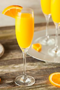 tall glass with mimosa and orange slice